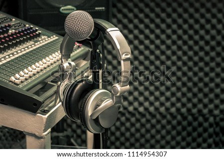 Close up instruments music background concept.Headphones hang  on microphone with sound mixer board in home recording studio.Free space for creative design text & wording mock up template wallpaper.