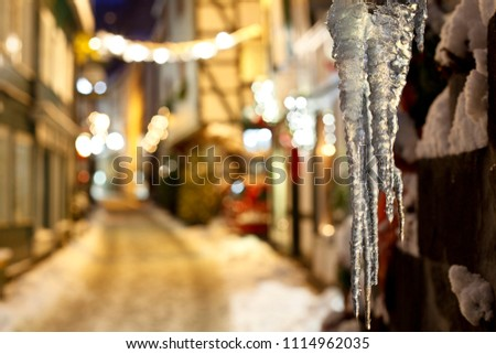 Icicles hanging in a small street in the German Eifel village of Monschau during christmas time at night. Focus on the icicles, Germany. Royalty-Free Stock Photo #1114962035