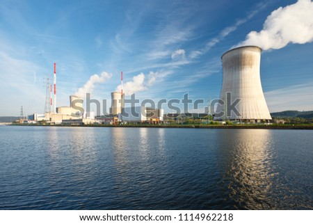 Daytime shot of a nuclear power plant at a river with blue sky and some clouds as well as reflection. #1114962218