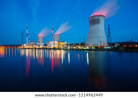 Night shot of a nuclear power plant close at a river with blue night sky. Royalty-Free Stock Photo #1114962449