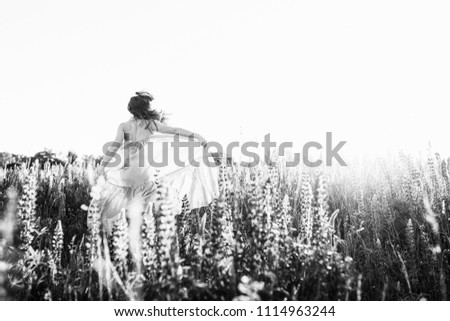 A beautiful bride in wedding dress dancing alone in field of lupine flowers on sunset. View from the back #1114963244
