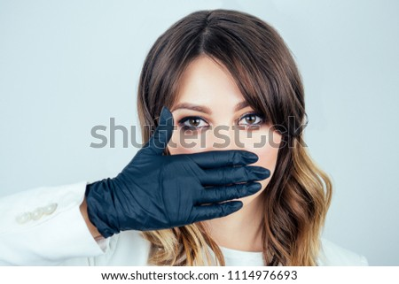 portrait of a beautiful and young doctor woman in white medical gown , black rubber gloves and black mask on face on a white background. the concept of silence and secret #1114976693
