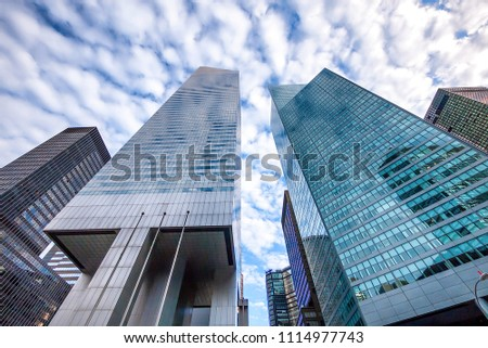 Upward view of tall New York City skyscrapers on a patchy cloudy #1114977743