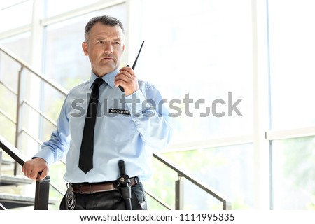 Male security guard using portable radio transmitter indoors #1114995335