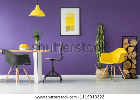 Dining table, black chairs, yellow poster, plants and firewood log rack in a modern dining room interior #1115013323