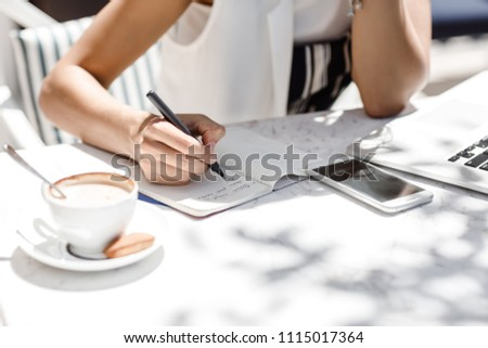 Hands of unrecognisable woman sitting at coffee shop and writing in her notebook. Royalty-Free Stock Photo #1115017364