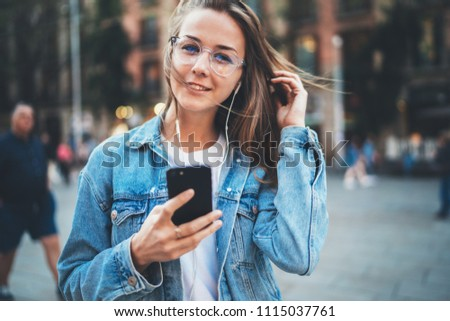 Beautiful positive girl with long blonde hair wearing trendy eyeglasses enjoying a walk in the city listening to music, cheerful woman wanderer in hipster look using modern smartphone outdoors #1115037761