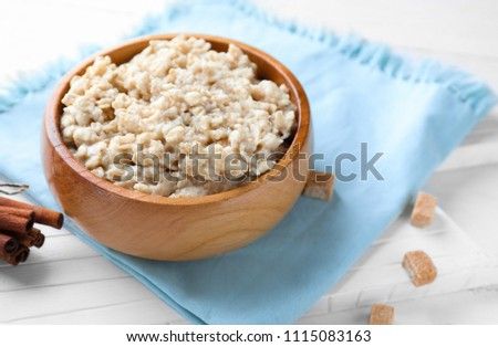 Tasty oatmeal in bowl on table #1115083163