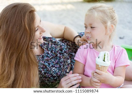 Mom and daughter eat ice cream. Happy family moment. #1115089874