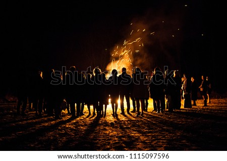 People standing next to a big beach bonfire with sparks flying around #1115097596