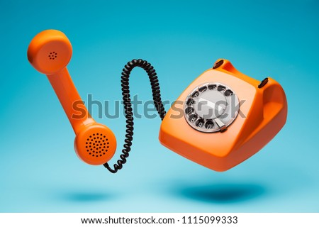 Old orange telephone rings with handset off. Royalty-Free Stock Photo #1115099333