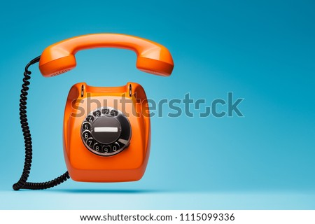 Old orange telephone rings with handset off. Royalty-Free Stock Photo #1115099336