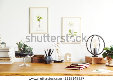Vintage, creative home office interior with wooden desk, books, notebooks, romantic illustrations of plants, table lamp and office accessories. Stylish space for freelancer. #1115148827