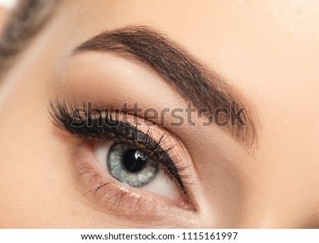 Eye of young woman with beautiful eyebrow after correction, closeup #1115161997