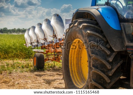 tractor with plough beside the field #1115165468