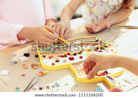 The mosaic puzzle art for kids, children's creative game. The hands are playing mosaic at table. Colorful multi-colored details close up. Creativity, children's development and learning concept #1115268500