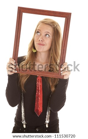 A teen girl looking up holding on to a picture frame with a silly expression.