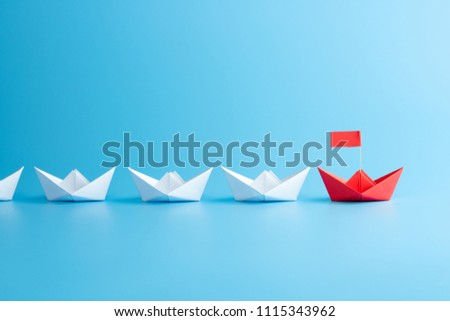 Leadership concept. Red leader paper ship leading among white on blue background. #1115343962