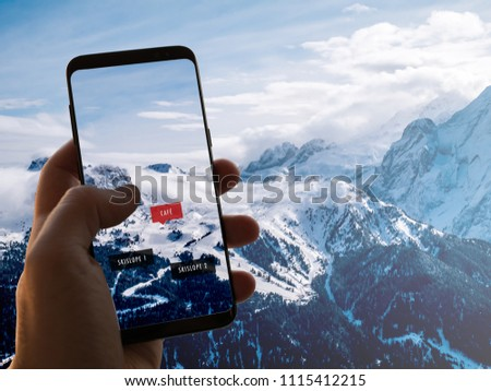 Augmented Reality (AR) information technology is displayed on a smartphone in the alps to guide and show information about café, ski slopes and restaurants on the screen. Hand is holding mobile phone. #1115412215