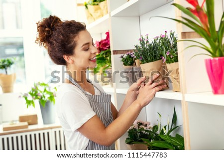 Flower retail. Nice good looking woman taking a plant while selling it #1115447783