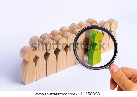 The chosen person among others. A human figure of green color stands out from the crowd. Wooden figures of people. A talented worker, a successful choice. Promotion. Concept of search for worker. #1115508581