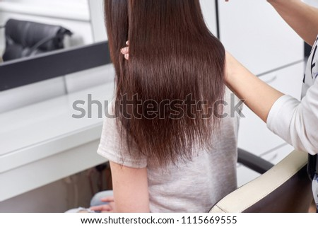 Closeup of hair stylist combing client's hair in salon #1115669555