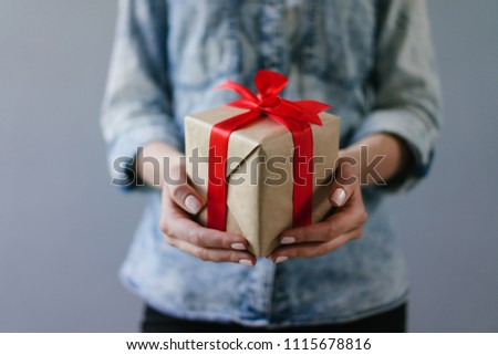 Close up cropped shot of a woman dressed in denim shirt  holding gift box wrapped in craft paper and decorated with red satin ribbon in her hands. Plain grey background. #1115678816