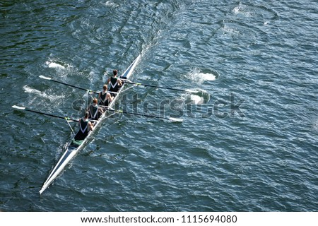 Top down view on a four person crew team, racing a rowing shell on a calm blue lake, with space for text on right Royalty-Free Stock Photo #1115694080