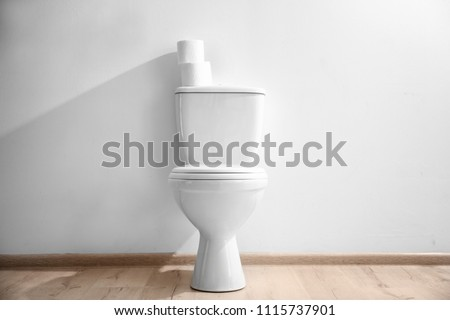 New ceramic toilet bowl near light wall #1115737901