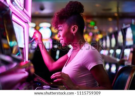 happy woman gambling at casino playing slot machine Royalty-Free Stock Photo #1115759309