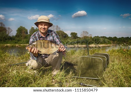 The fisherman holds a large bream in his hands, an excellent catch. Fishing on the Dnieper River in summer. #1115850479