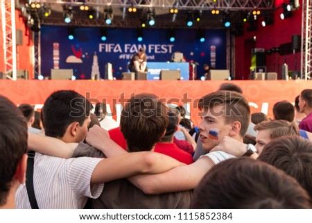 Rostov-on-Don, Russia, 06/17/2018, World Cup 2018, Football fans are standing in front of the stage at the Fan Festival, hugging each other by the shoulders.  #1115852384