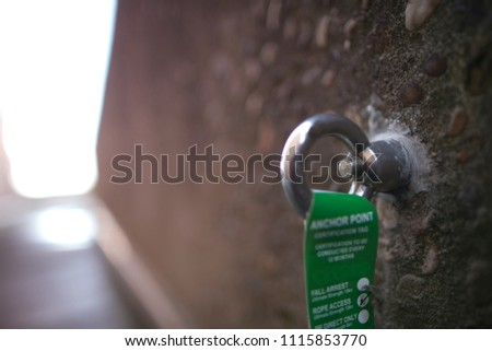 Safety workplace industrial rope access working at heights fall arrest, abseiling stainless ring 16 MM dimension certifies anchor point installed on concrete wall construction building site