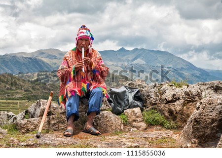 The old man Quechua dressed in a colored poncho and a cap of Chullo, sits on the rocks with a view of the mountains in the background and plays on the musical instrument of Quena. Cusco, Peru. #1115855036