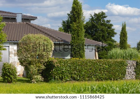 house of rural village on horizon under blue sky near corn field in south germany countryside #1115868425