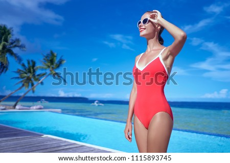 Summer vacation and fashion. Beautiful young woman in red swimsuit near swimming pool on tropical beach. #1115893745