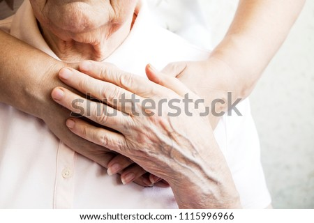 Mature female in elderly care facility gets help from hospital personnel nurse. Senior woman, aged wrinkled skin & hands of her care giver. Grand mother everyday life. Background, copy space, close up #1115996966