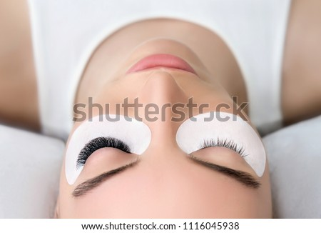 Eyelash Extension Procedure.  Beauty Model with  Perfect Fresh Skin and Long Eyelashes. Slincare, Spa and Wellness. Make up,  Hair and Lashes. Close up. Royalty-Free Stock Photo #1116045938
