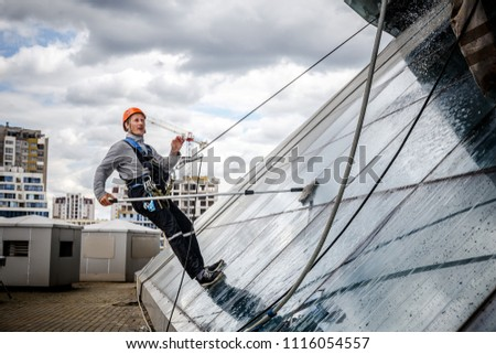 MINSK, BELARUS - 02 JUNE. 2018: group of workers cleaning windows service on high rise building. work on the heights , industrial mountaineering #1116054557