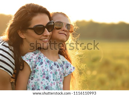 Happy fashion kid girl embracing her mother in trendy sunglasses and looking on nature background. Closeup portrait of happiness. #1116110993