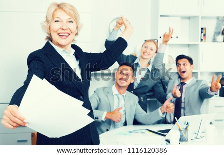 Happy team with businesswoman on foreground emotionally gesturing and celebrating victory at office #1116120386