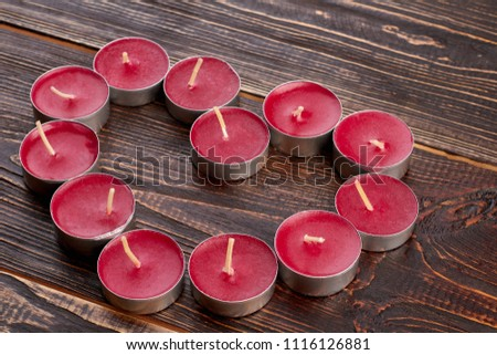 Shape of heart from tea light candles. Beautiful heart shaped decoration from scented candles on brown wooden background. #1116126881