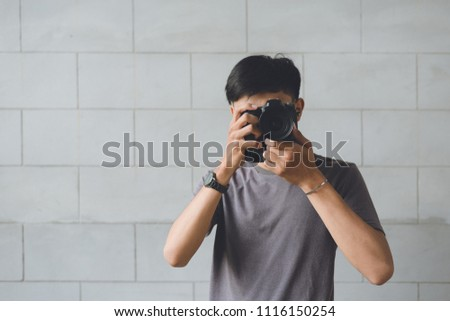 Asian young man uses a camera