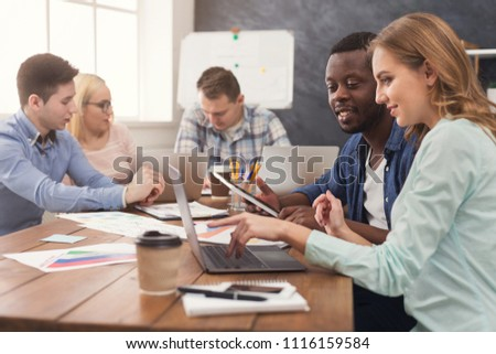 Happy business partners working in modern office. Two worried multiethnic coworkers discussing new project while working on laptop, copy space #1116159584