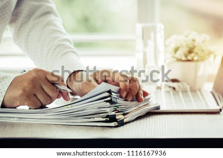 Businessman hands holding pen for working in Stacks of paper files searching information business report papers and piles of unfinished documents achieves on laptop computer desk in modern office #1116167936