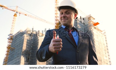 Portrait of a successful young handsome engineer, architect, builder, businessman, wearing a white helmet, in a suit, looking, skyscraper background and building. #1116173279