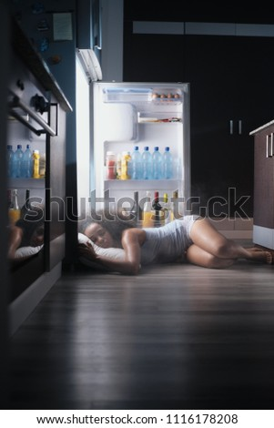 Young hispanic woman suffering for summer heat and lack of air conditioning at home. Black girl covered with sweat sleeping on floor with head inside fridge. #1116178208
