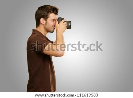 Man Holding Camera On Gray Background #111619583