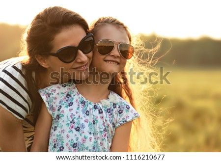 Happy fashion kid girl embracing her mother in trendy sunglasses and looking on nature background. Closeup portrait of happiness. #1116210677