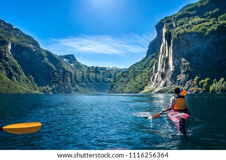 "young man kayaking along the fjord geiranger enjoying the waterfall ""seven sisters"" #1116256364"